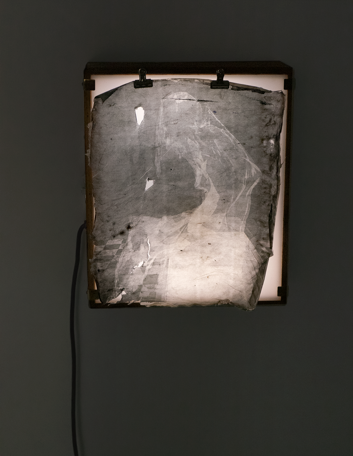 A black and white print on transparent paper is held up by a clip above a lightbox that illuminates it similar to an x-ray. The image, not easily decipherable, is an alternate angle of the video in the series, in which a veiled, 500-year old Mona Lisa sits on top of a medical exam table.