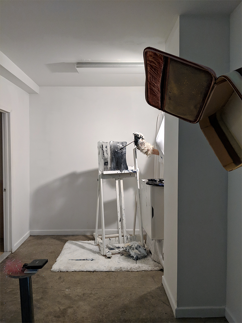 A wide angle vertically-oriented digital photograph documenting a performance in a white gallery with cement floors. In the center of the image two blocks of ice rest on a white easel. A human arm with a sock puppet-like polar bear arm attachment holds a paintbrush and reaches through a white curtain to paint the blocks of ice. Water and acrylic paint can be seen dripping down the easel and onto the plush white carpet below.
