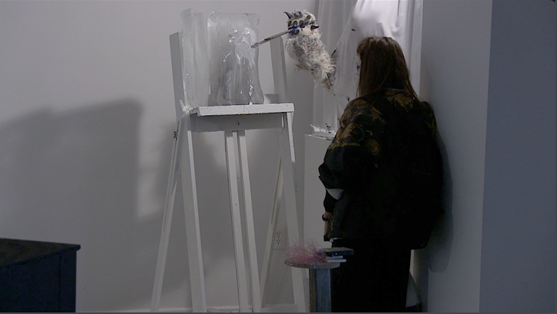 Medium angle a performance documentation still. Two blocks of ice both roughly the size of a shoe box rest atop a white easel. A costumed polar bear arm with claws hold a medium size paint brush and can be seen applying big gobs of white paint onto the surface of the ice where it is melting. A human spectator stands in the foreground watching the performance. A white curtain protects the human puppet master wearing the polar bear arm from being seen but the outline of their forehead pressed up against the sheet can be seen.