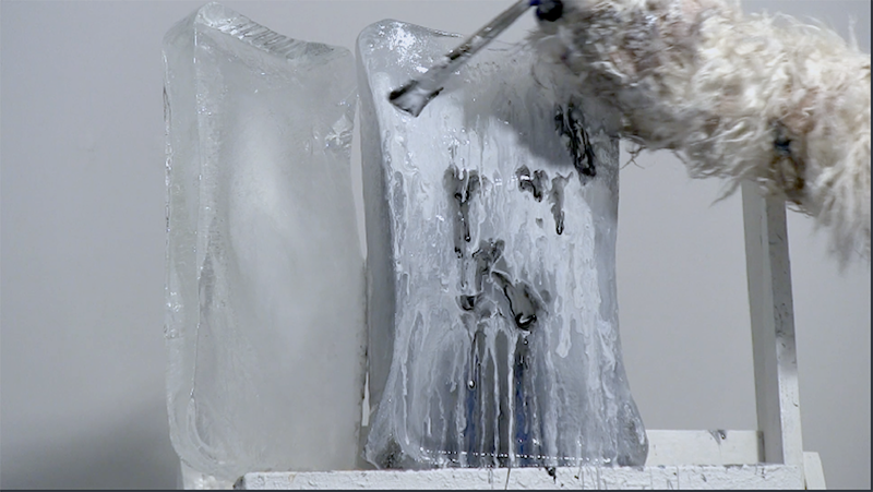 Closeup of a performance documentation still. Two blocks of ice both roughly the size of a shoe box rest atop a white easel. A costumed polar bear arm with claws hold a medium size paint brush and can be seen applying big gobs of white paint onto the surface of the ice where it is melting.