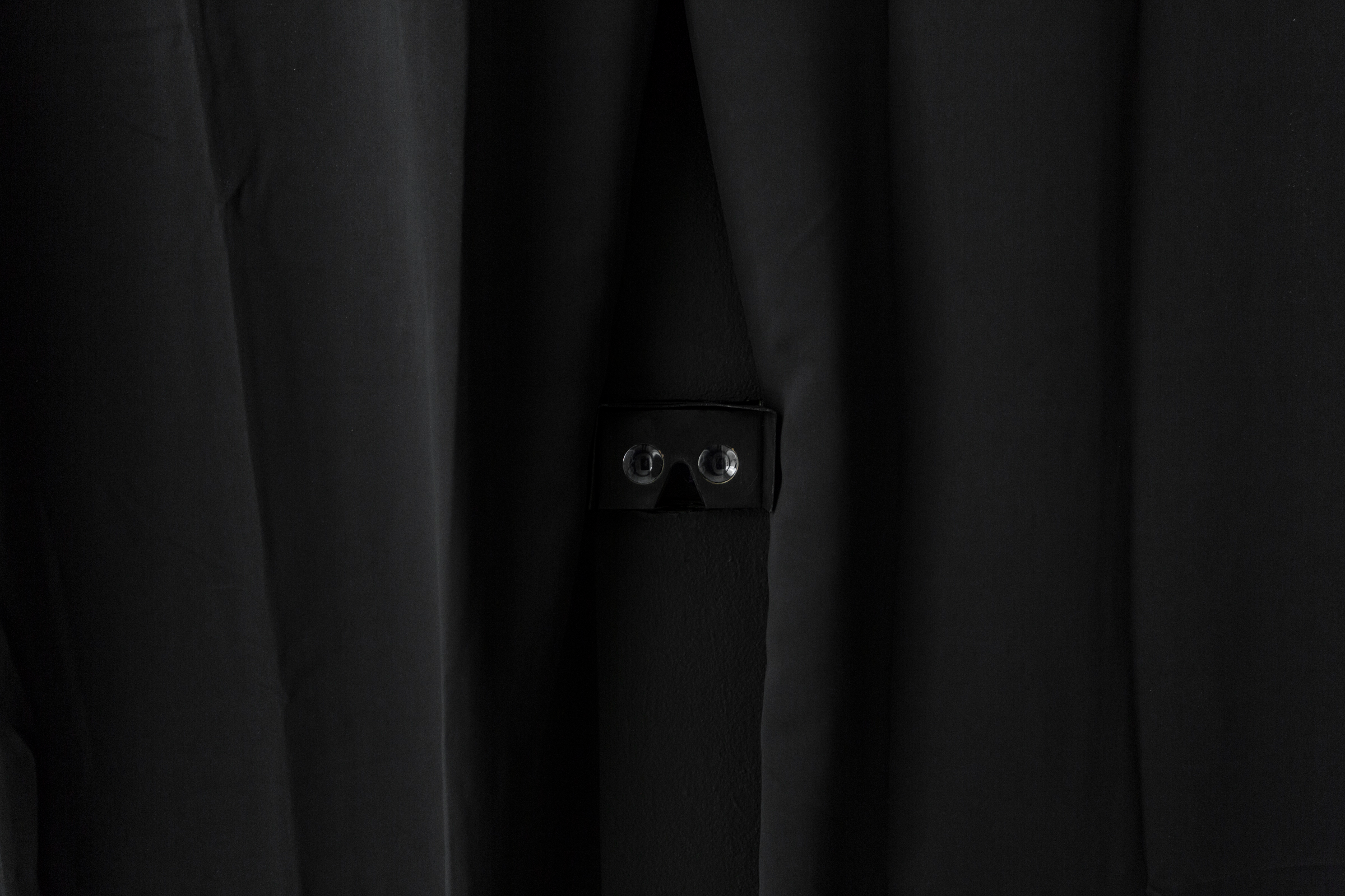 a medium close-up shot of the Google cardboard device embedded in a black wall and surrounded by black curtains. The viewer uses this as a peephole to peer into the virtual reality experience, made possible by stereoscopic image technology on a phone.
