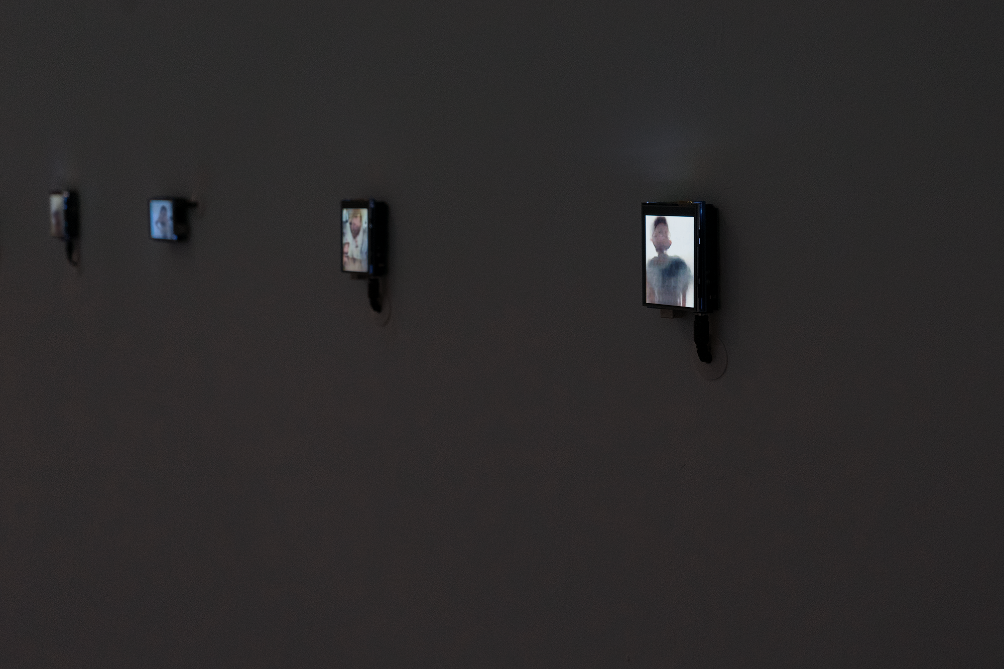 A medium angle photo of four (out of 10 total in the installation) bright LCDs displaying a static image that loosely resemble human beings. The screen is attached to a microcontroller and hangs on the wall with four pushpins. A 12 volt power supply connects at the bottom of the microcontroller and then threads into the wall.