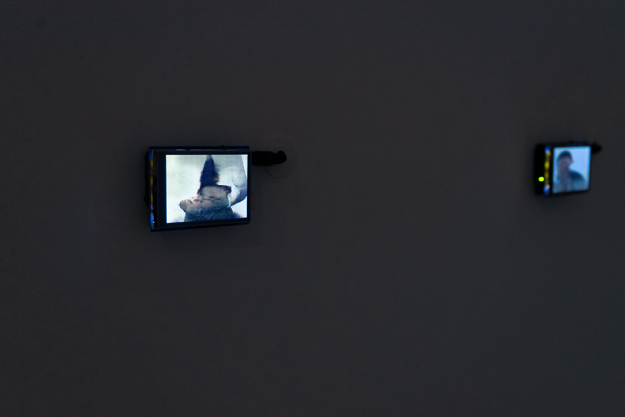 A closeup photo of two (out of 10 total in the installation) bright LCDs displaying a static image that loosely resemble human beings. The screen is attached to a microcontroller and hangs on the wall with four pushpins. A 12 volt power supply connects at the bottom of the microcontroller and then threads into the wall.
