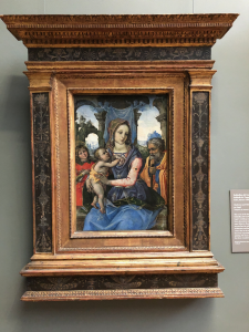 My image description: As the title describes, there are four figures in the painting who take up most of the lower half of the painting, with the Madonna located most centrally and prominently amongst them. She holds her baby, who stands somewhat upright on her right thigh and places his hands right above his mother's nipple on her unclothed breast. The four figures have brightly-colored draped fabric garments while the landscape behind them is in ruins, with two large arches to either side of the Madonna that look like they are in a state of being of reclaimed by vegetation and forests.